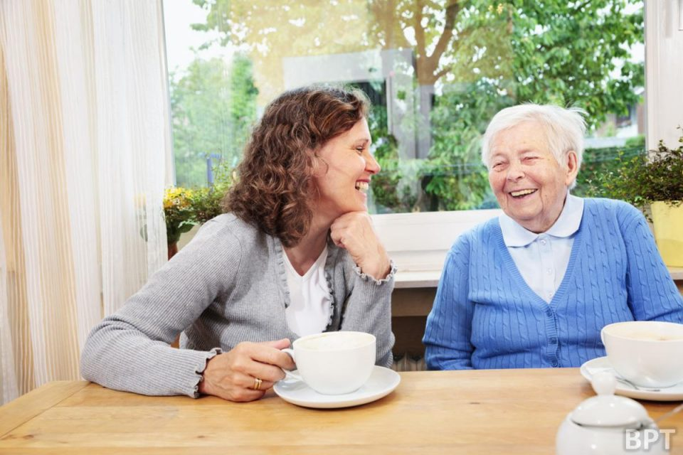 senior woman and caregiver talking  laughing